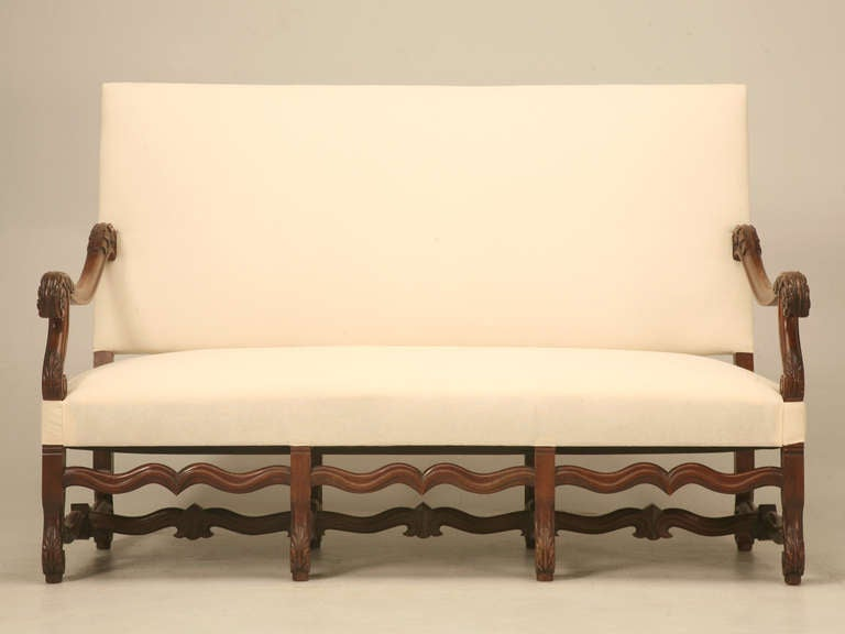 Circa 1890 French three seater sofa in the style of Louis XIV. Solid walnut frame, with new hand tied spring seat with proper horse hair padding. The newly tightened arms have a graceful floral motif. The legs and stretcher are classic os de mouton.