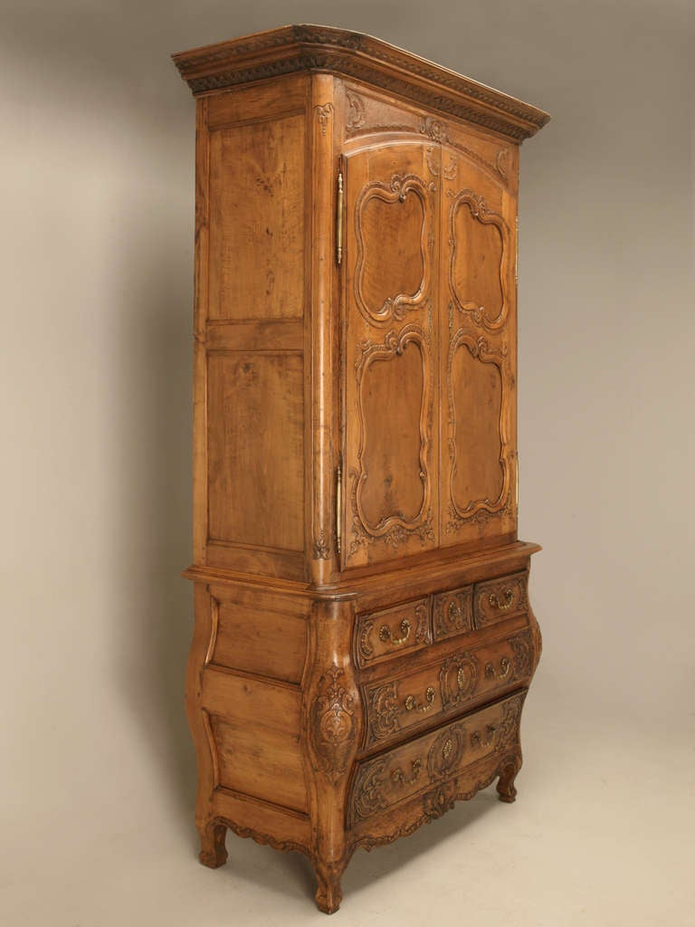 French walnut armoire, or as the French would call it; a commode buffet Louis XV. The bottom portion is bombe and the top has very old toile fabric inside and we just had to leave it alone. We rarely if ever see useable fabric on the interior of an