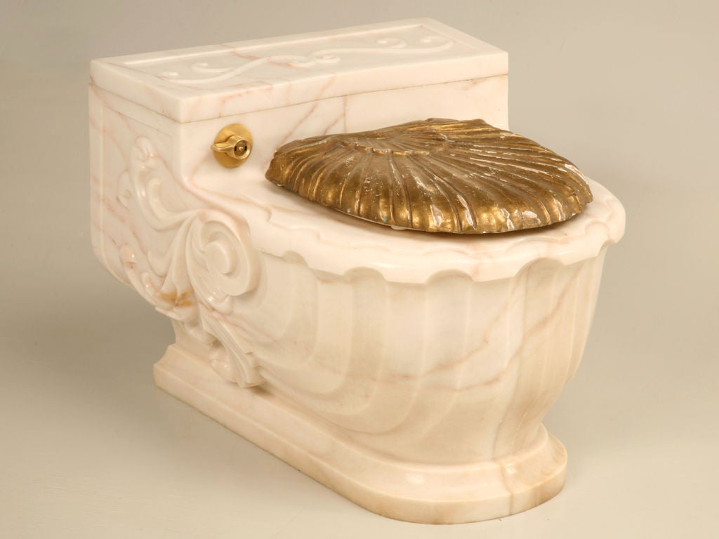 A magnificent work of art--this fine Sherle Wagner commode cover is still being sold today. Ingeniously designed to slide over a wall mounted commode, this scroll and flourish casing is the ultimate in luxury. Designed in a Aurora Marble Rose