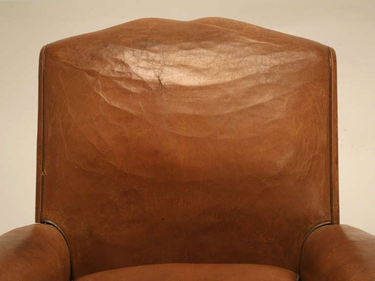 Pair of French club chairs in their original leather, circa 1930s. Like all the club chairs we offer for sale, each and every chair has the bottom opened for a thorough inspection to ascertain what is required before it can be sold. At the bare