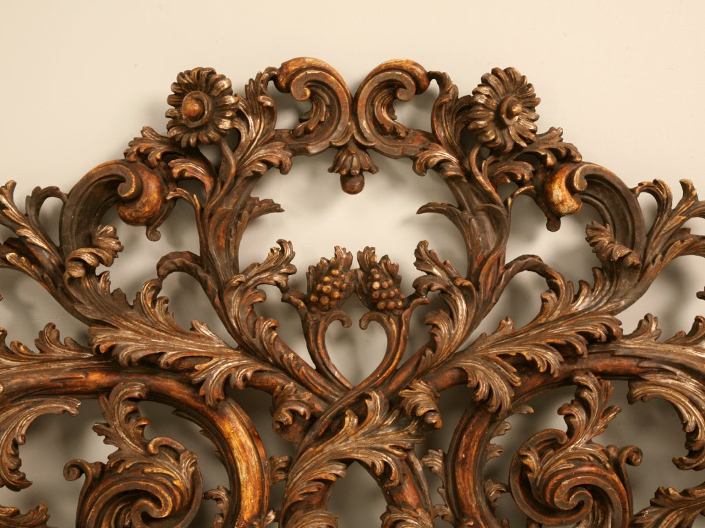 Mesmerizing original antique Italian carved and gilded architectural organic relief that would be perfect as a king sized headboard. This spectacular carving showcases scrolling vines studded with leaves, flowers and clusters of grapes. There are so
