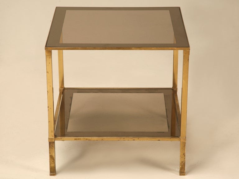 Fantastic French Mid-Century design, this quaint cube table has plenty to offer for its petite size. Square shaped legs elegantly support the two floating smoky glass shelves with their mirrored borders. Clean lines paired with minimalist decoration