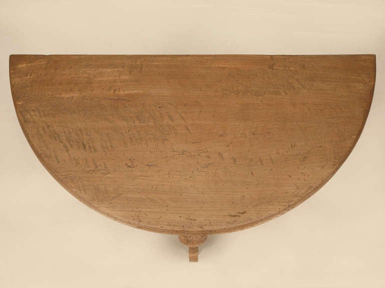 With a restored finish to the top and lower shelf, this antique French white oak table offers unique hand carved elephant legs. Structurally sound.