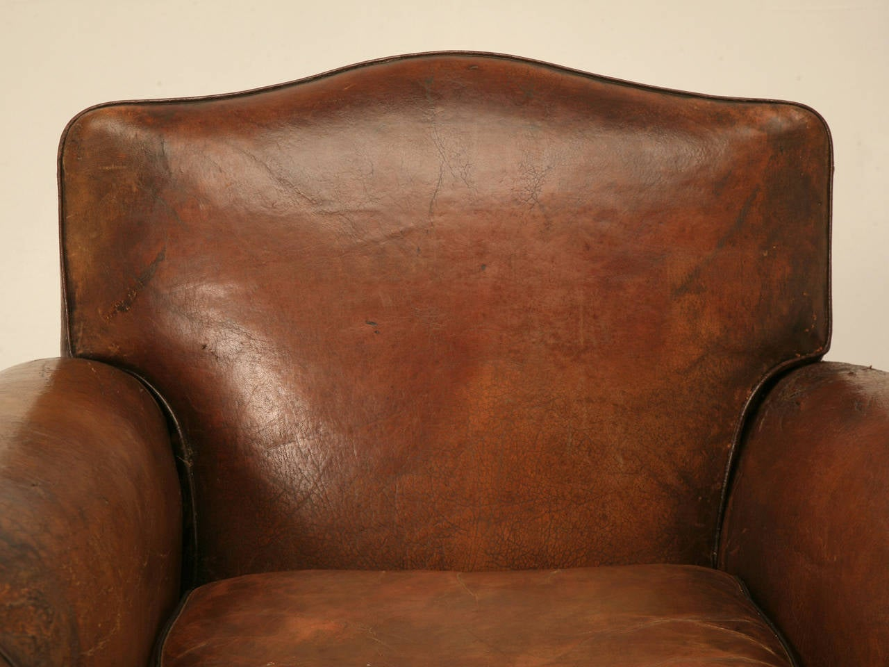 Circa 1930'2 French leather club chair. We rebuilt the chair from the bare frame up while not disturbing the original leather covering. Springs were eight way hand tied, and any padding required was horsehair. This particular model is larger and
