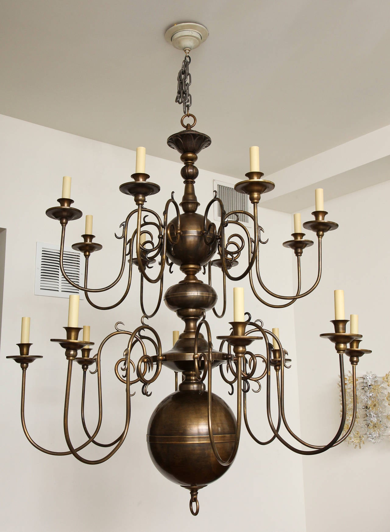 A two-tier sixteen-light Dutch style chandelier with rubbed bronze finish and oversized ball at underside with raised horizontal line at centre. The centre shaft with round and bun shaped elements. Fixture fitted with sixteen candelabra sockets.