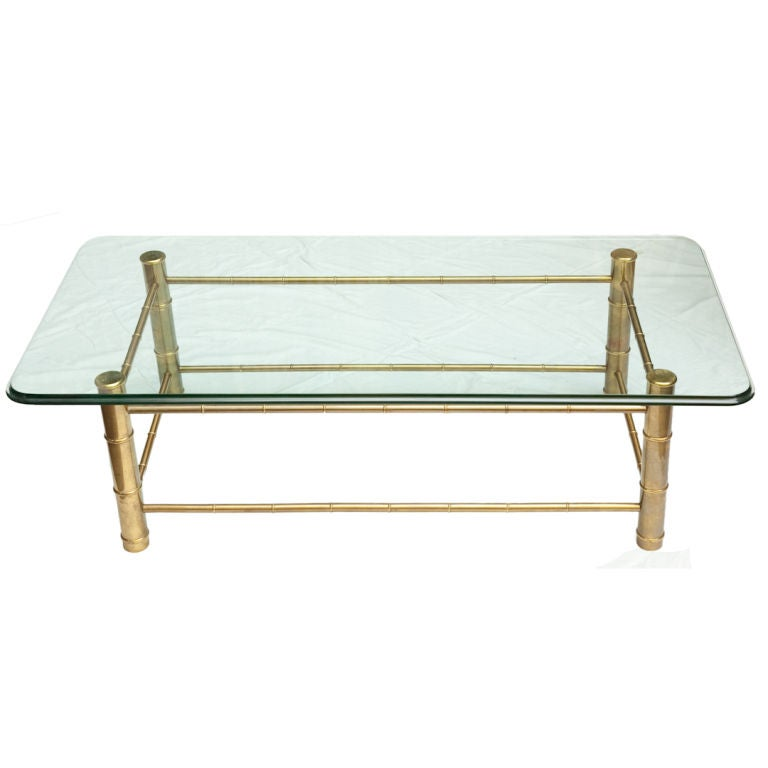 A Rectangular Coffee Table With Brass Base And Faux Bamboo
