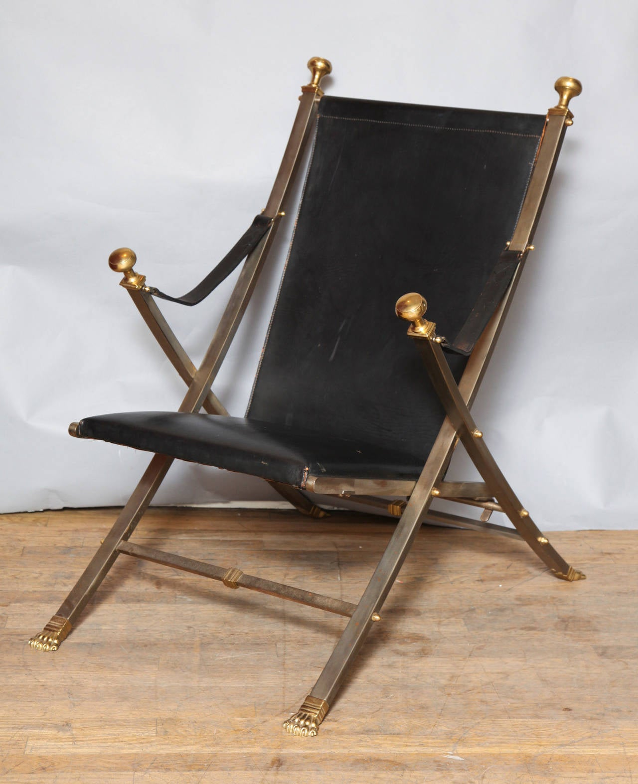 A pair of Jansen-style Campaign chairs, the X-shaped frames with leather upholstered seats and backs. The steel frames accented with brass lines, paw feet, and finials. The same model was fabricated by Jansen and documented in the Jansen monograph