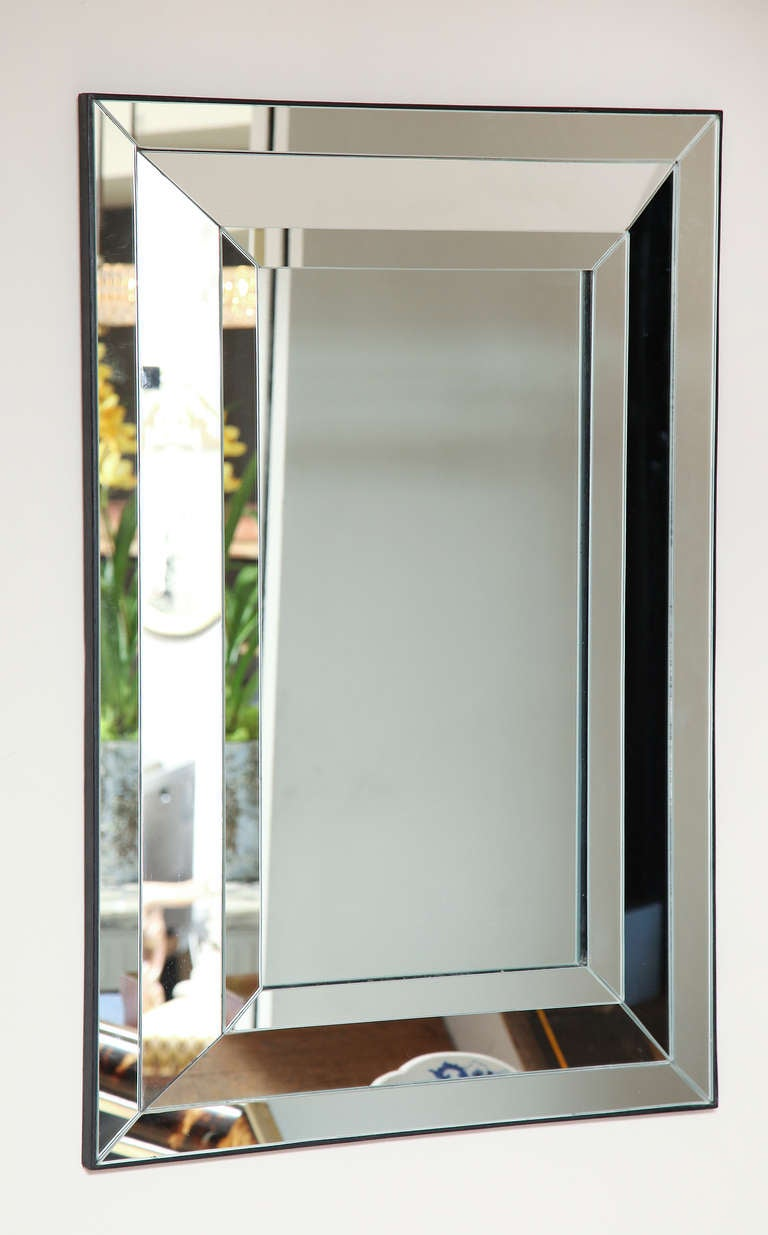A contemporary design mirror with rectangular frame with mitered strips of mirror surrounding rectangular center glass.