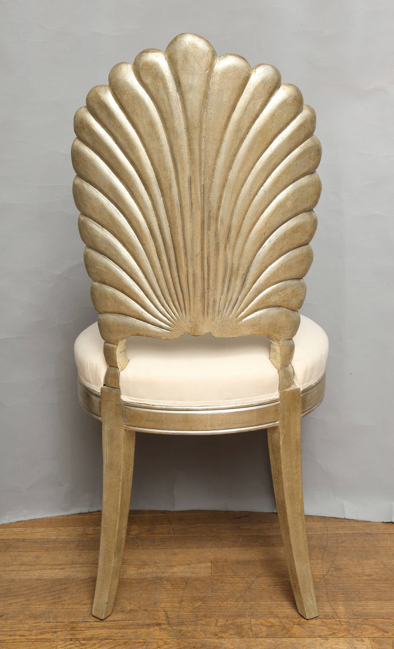 An italian shell back carved and silver leafed chair for