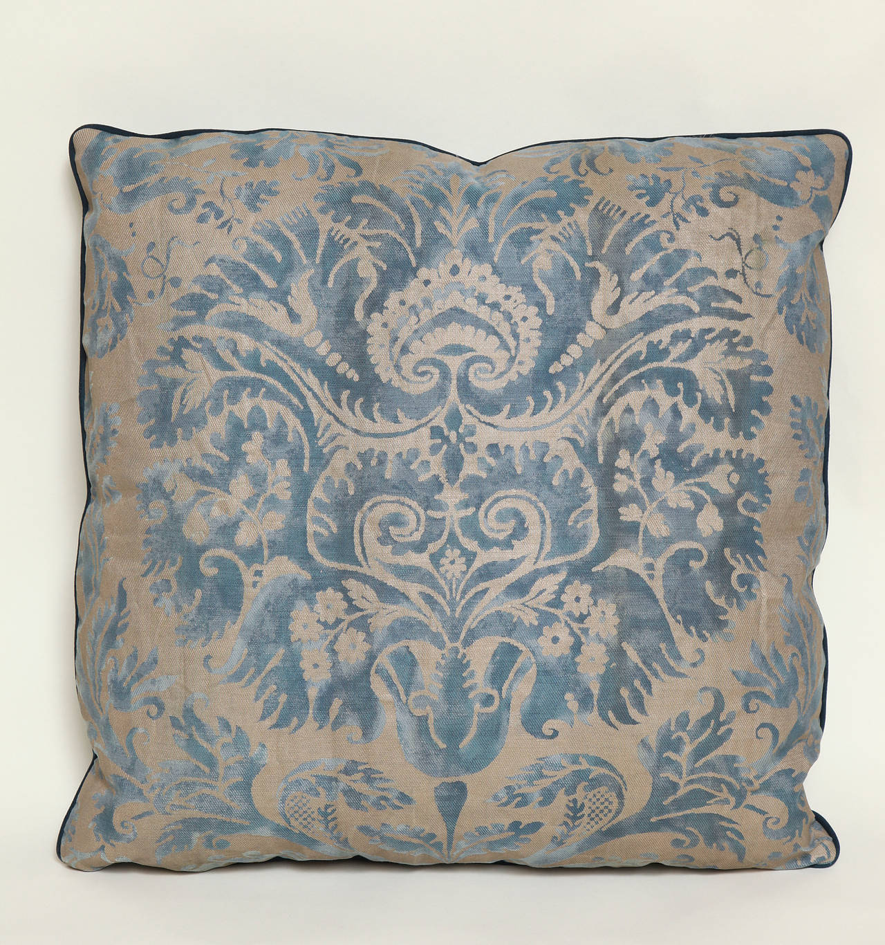 A Fortuny fabric cushion in the Demedici pattern, patinated silver ground and welt trim with midnight blue wool sateen back, the pattern, a 17th century Italian design named for the famous Florentine banking family, political dynasty and royal