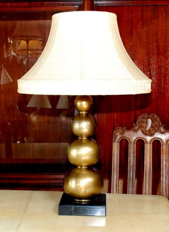 Single brass table lamp with black marble base.