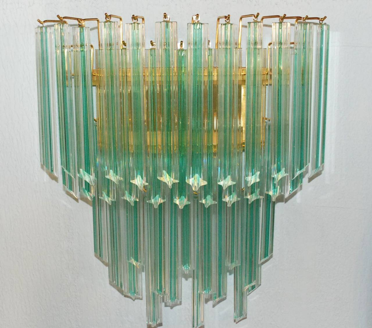 A pair of Venini aqua stripe (clear and aqua) sconces. Each sconce has two lights with brass frame and decorated with solid quadriedri (four-sided) hanging Murano glass tubes.