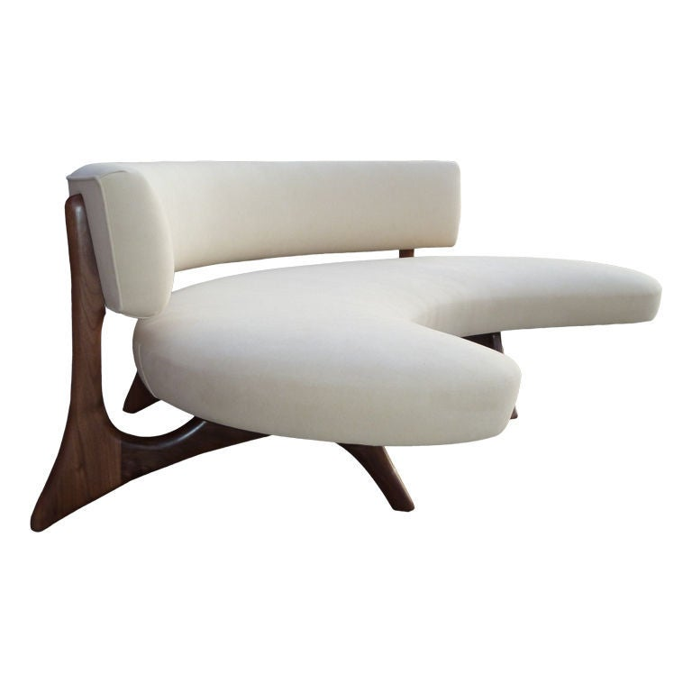A biomorphic walnut sofa with curved backrest and a floating platform seat set on sculptural carved legs which blend seamlessly into the support for the back. A reproduction inspired by the amazing design of Vladimir Kagan.
