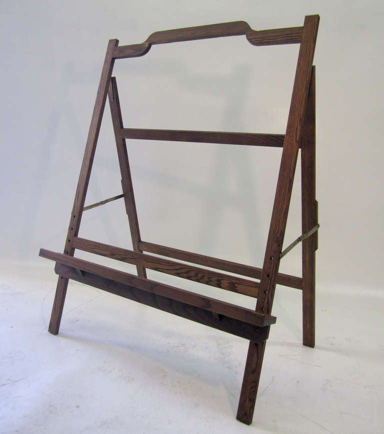 This large, Mid-Century Modern easel in stained oak (?) is an ideal piece for artists and collectors alike. The sturdy easel is fully adjustable including the deep shelf which may be moved up and down to accommodate your artwork. Its size is rare.