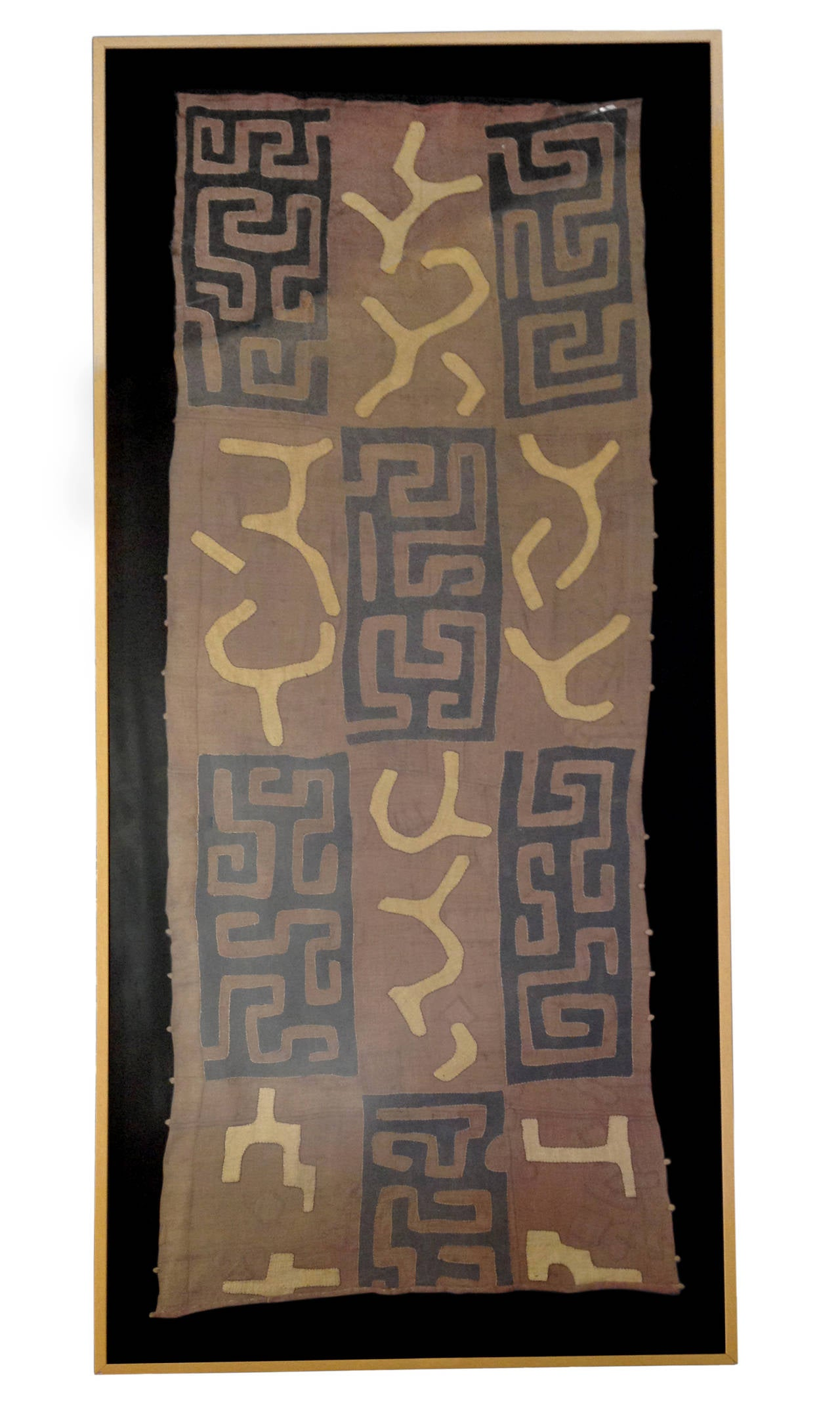 A framed textile created by the Kuba of the Democratic Republic of the Congo. These traditional textiles are created from raffia cloth dyed with twool, a pigment harvested from the heart of certain African tree species. Multiple layers of this cloth
