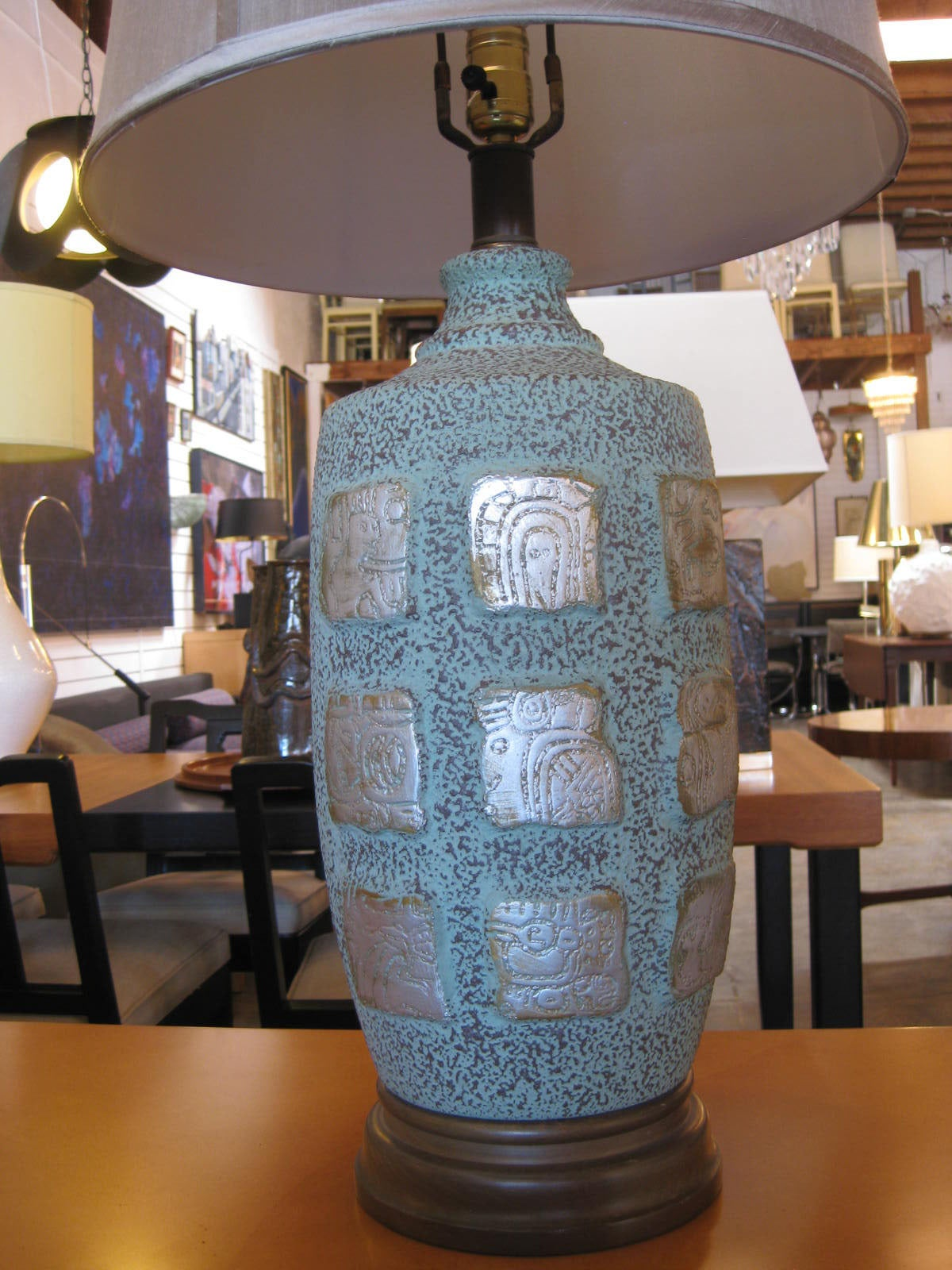 Handsome pair of light teal ceramic table lamps with wooden base. Eighteen silver plated Mayan hieroglyphs, 9 per each side, decorate the frontal of each piece. The base is made of solid wood. Included, as shown with each lamp is a 16