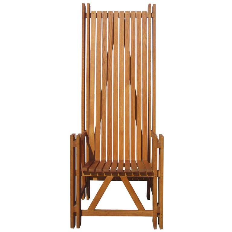 This architectonic high-back armchair inspired by Charles Renee Mackintosh features a form composed of slatted teak.