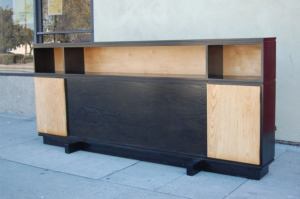 This Mid-Century Modern headboard features a cabinet on each end that opens up to reveal shelving inside. The piece has been stained ebony throughout with the exception of the doors and the back which have been left natural. A platform has been