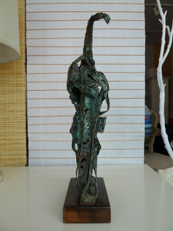The work of art is twisted and contorted which illustrates motion. It rests on a wood block base.