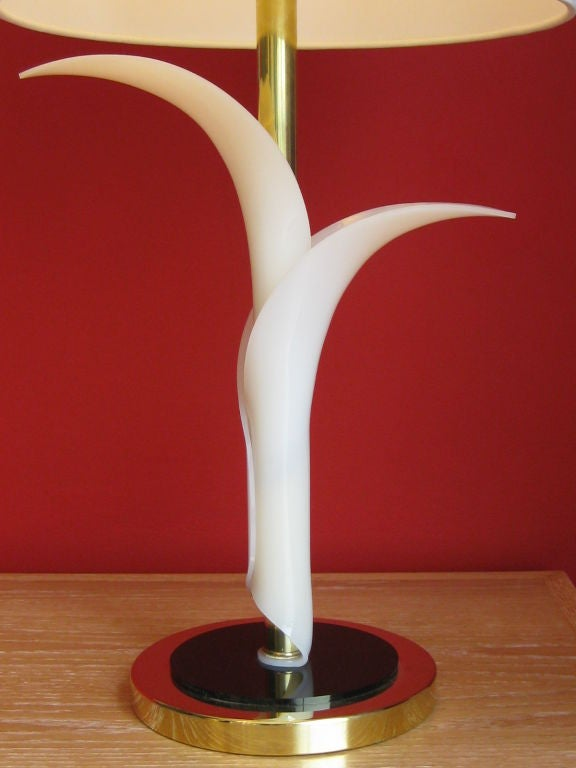 Table lamp composed of 2 white acrylic leaves on a brass and black lucite base.