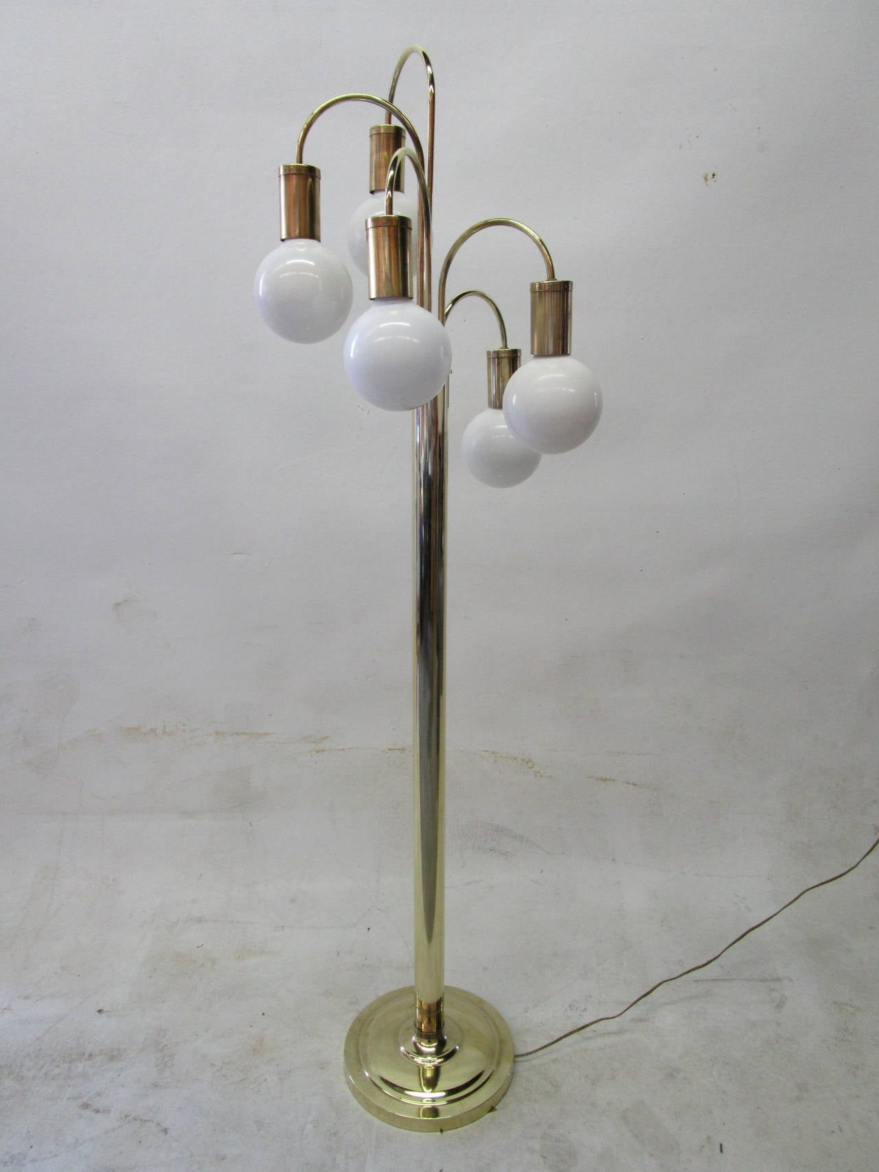 Five curved branches radiate from the central cylinder in a helix and each ends in an opaque white globe bulb. The lamp is operated by a dimming dial that controls the intensity of the light.