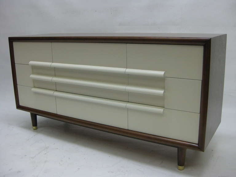 This mid-century modern dresser by Furniture Guild of California features a walnut casing housing nine drawers finished in cream lacquer. Four tapered legs capped with brass feet support the piece. * We also have the matching nightstands and four