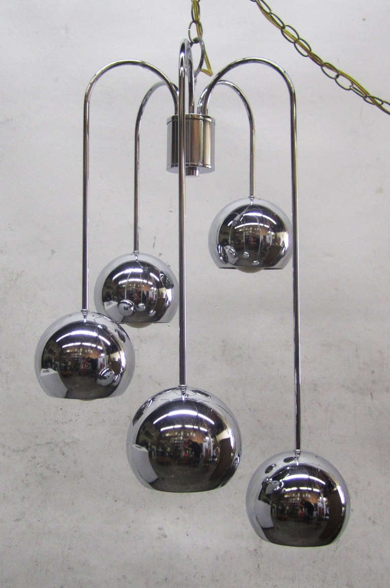 This hanging ceiling light from the 1970s features five polished chrome balls that arc from the center and spiral downwards.