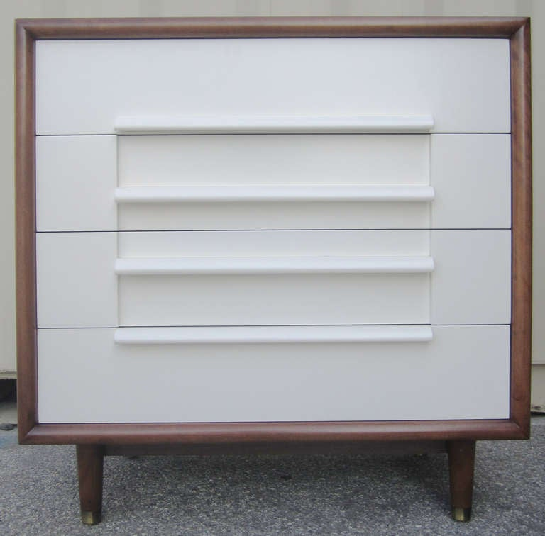 This mid-century modern dresser by Furniture Guild of California features a walnut casing housing four drawers finished in cream lacquer. Four tapered legs capped with brass feet support the piece.
