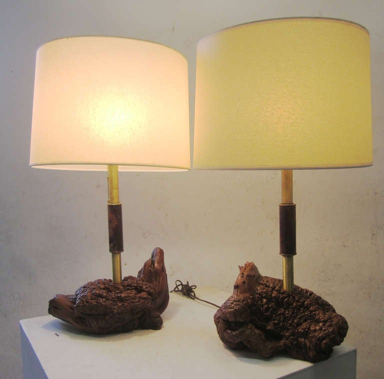 These outstanding lamps feature organic burled wood bases juxtaposed with tubular brass necks that are embellished in the centre with a cylindrical burled wood fitting. The Mid-Century Modern lamps have parchment-like, paper shades topped with brass