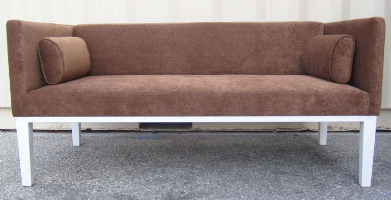 This handsome Mid-Century Modern loveseat features a tuxedo frame upholstered in brown chenille and complimented by a pair of rounded pillows. The comfortable, two-seat sofa rests on a white powder coated metal base.