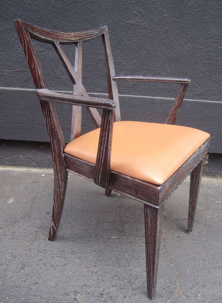 One captain's chairs and 5 side chairs by Paul Frankl newly refinished in a burnt amber stain and a cerused finish. Seats have been newly re-upholstered in cognac-toned leather.