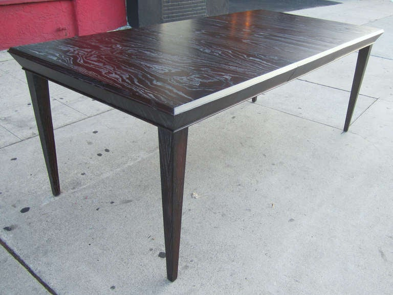 Paul Frankl dining table featuring beveled edges, tapered legs, newly refinished in a burnt amber stain with a cerused finish. There is an additional 12