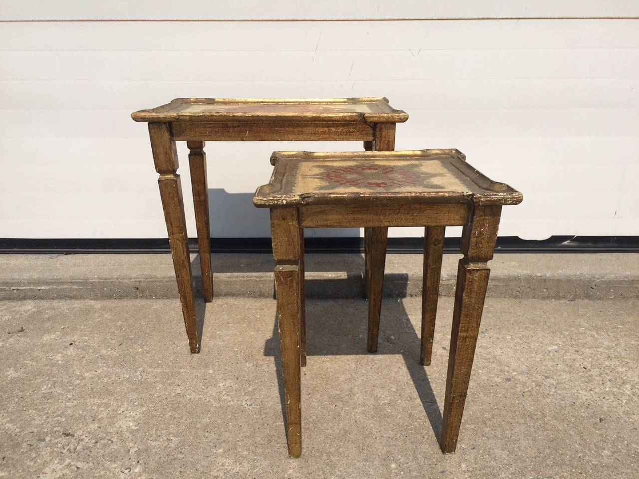 Set of two poly-chromed and heavily decorated Beechwood Nesting Tables.  Incredibly useful and decorative.  Use either together or apart.  Italian made circa 1900.  Smaller table measure H. 17.5