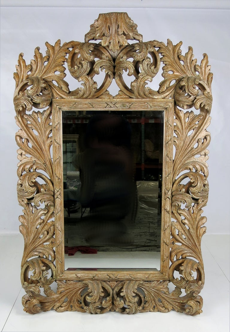 Fantastically and deeply carved Rococo style mirror with natural finish and beveled mirror.