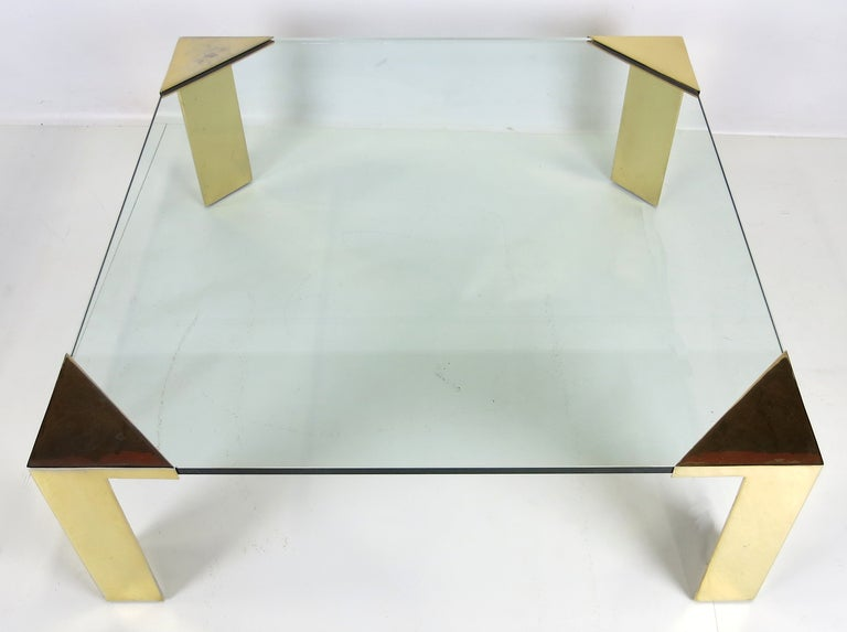 Impressive scale coffee table with brass plated steel legs. The large scale corner fixtures holds a 3/4