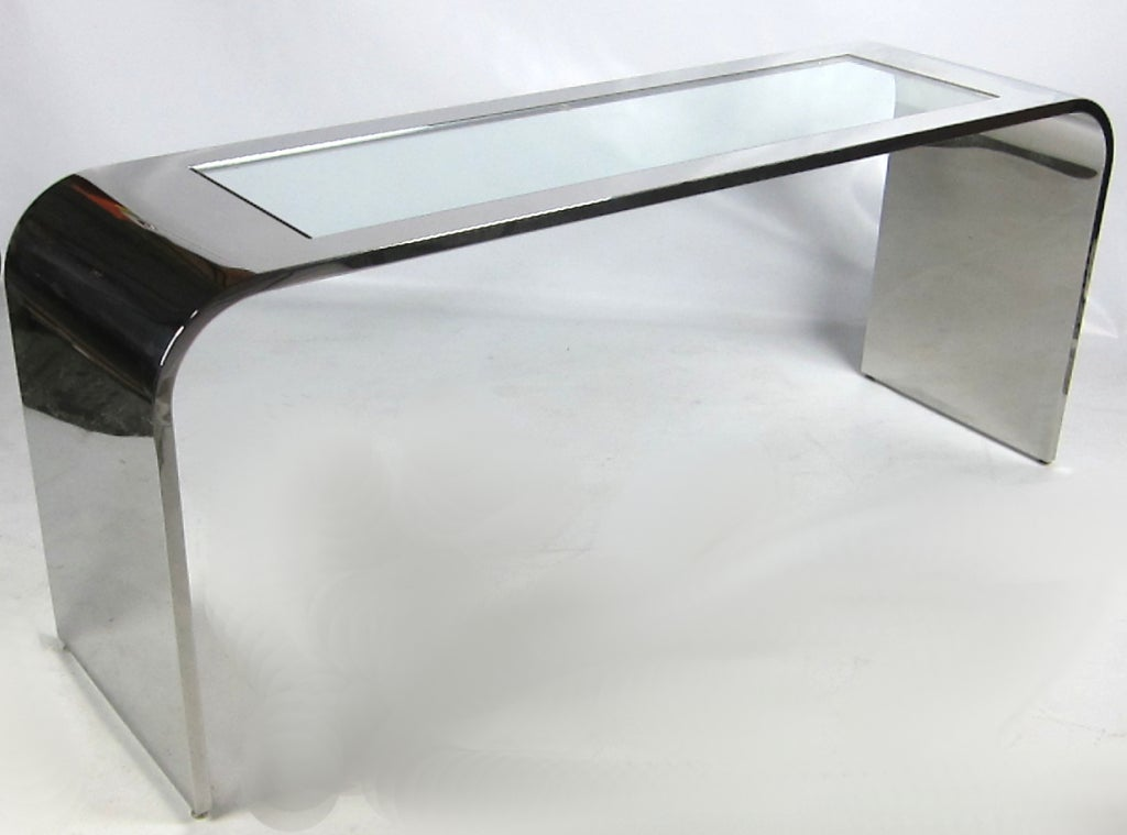 Large-scale mirror polished stainless steel console or sofa table with inset glass top by Stanley Jay Friedman for Brueton. Raised on adjustable steel glides. Top quality materials and workmanship throughout on this very impressive piece.   From