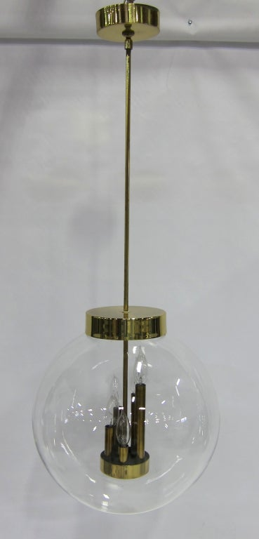 Large scale and fine quality clear glass globe Chandelier or pendant lamp with brass mounts by Robert Long Lighting.