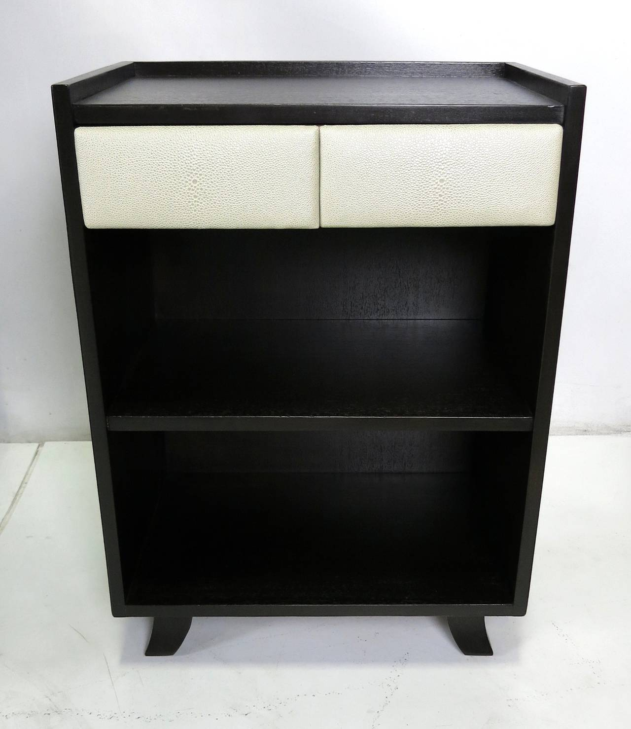 Pair of mahogany nightstands or side tables by Gilbert Rohde for Herman Miller. The stands have been meticulously restored in dark brown lacquer and the original Naugahyde drawer fronts have been freshly reupholstered with faux shagreen.