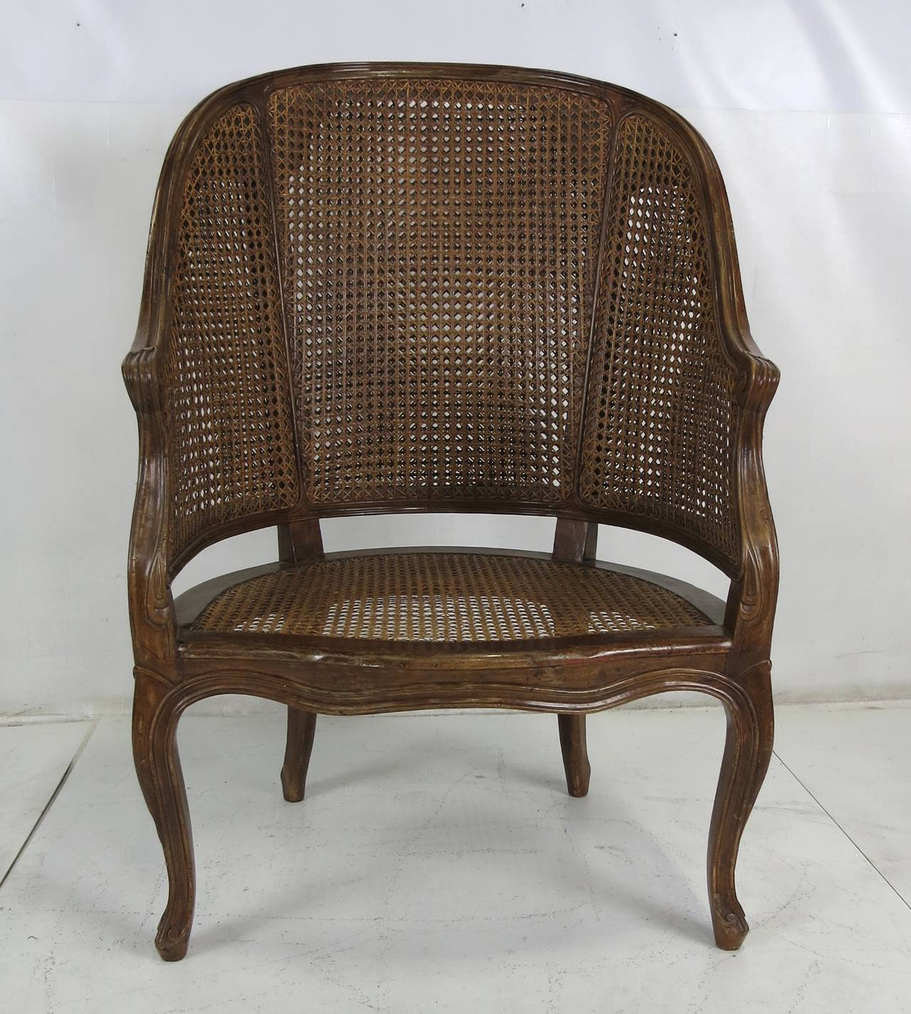 Beautifully carved and crafted Louis XV style barrel chair with hand-caned seat and double-caned back. Branded on bottom,