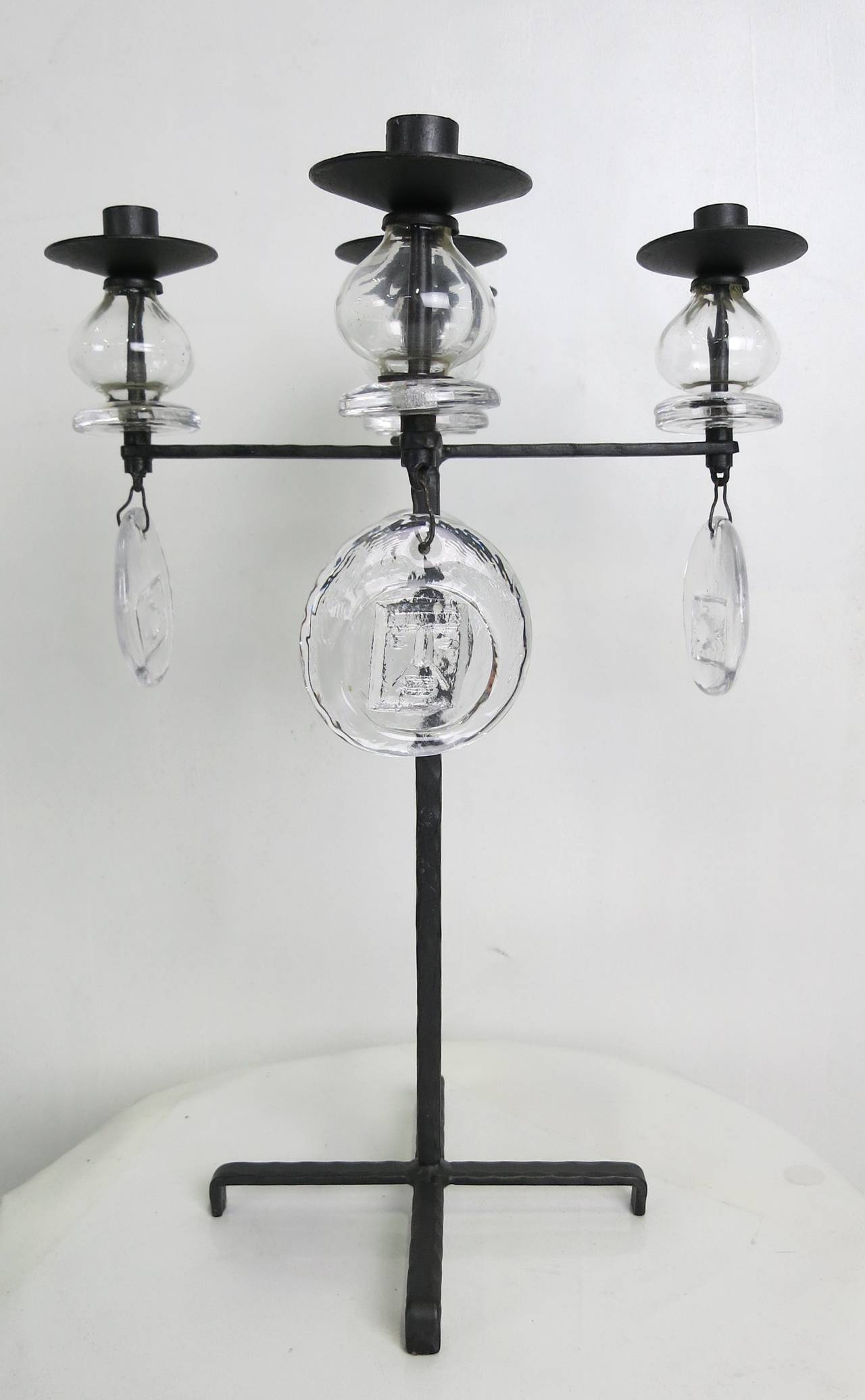 Rare and beautiful form candelabrum by Erik Hoglund for Kosta Boda. The hammered iron frame supports four arms and a central candle cup all raised on poppy form glass bulbs with round glass drops cast with signature Hoglund icons. The piece is in