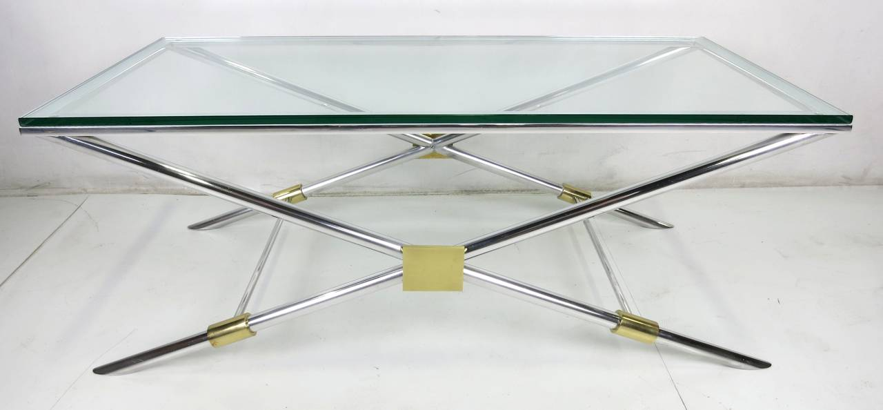 Rare neoclassical modern coffee table in aluminum and brass by John Vesey. The two X-form legs with brass cuffed stretchers support an aluminum frame for the flat polished edge glass top. The table has been painstakingly restored and hand polished