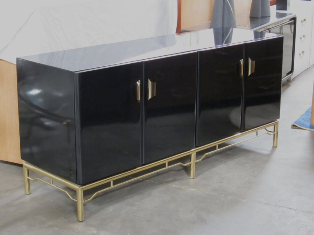 Black Lacquer Credenza or Buffet raised on a Brass base with Oriental fretwork stretchers.  Compartments have adjustable shelving and pullout drawers.  Exceptional lacquer finish with a fitted glass top.