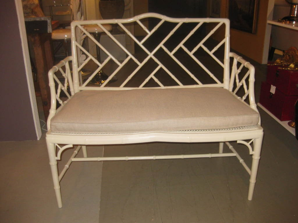 A painted faux bamboo settee with a new Belgian linen cushion