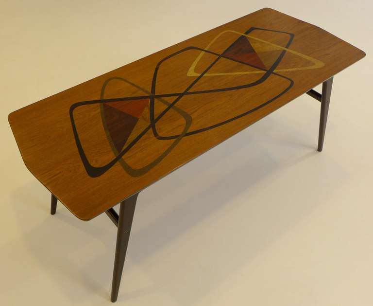 Cocktail table with abstract pattern of inlaid woods including Macassar ebony, cherry, olive, yellow oak, and bird's-eye maple. Made in Italy, circa 1953 and imported to the U.S. by Erno Fabry Associates. For an example with similar inlay see Rago,