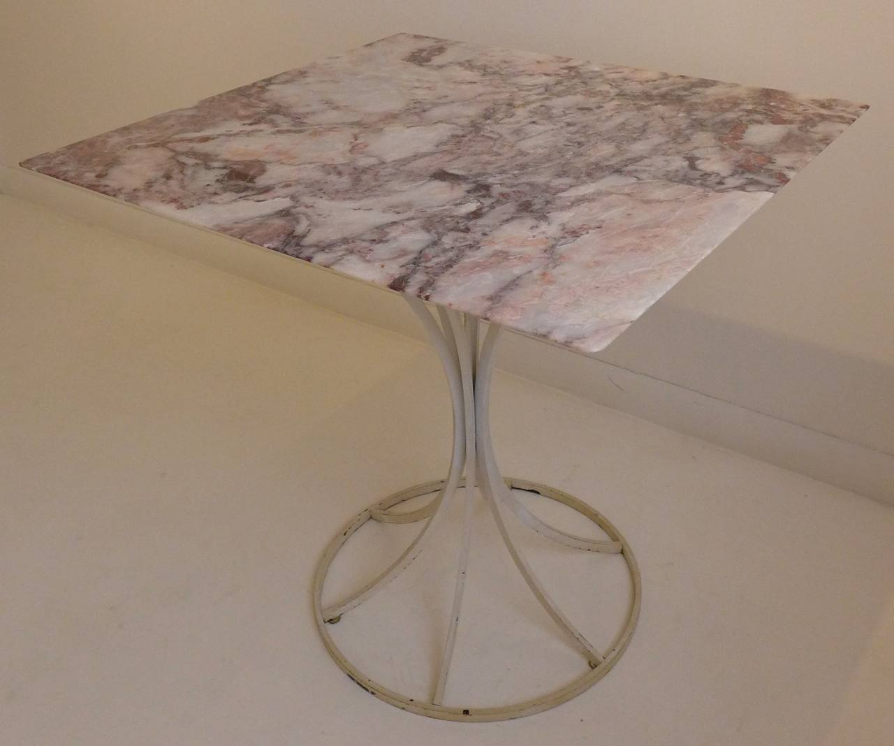 Dining or cafe table with highly figured rose marble top and lacquered steel petal base. Designed by Estelle and Erwine Laverne as part of their 1960s flower stem table line. A custom order with a 29