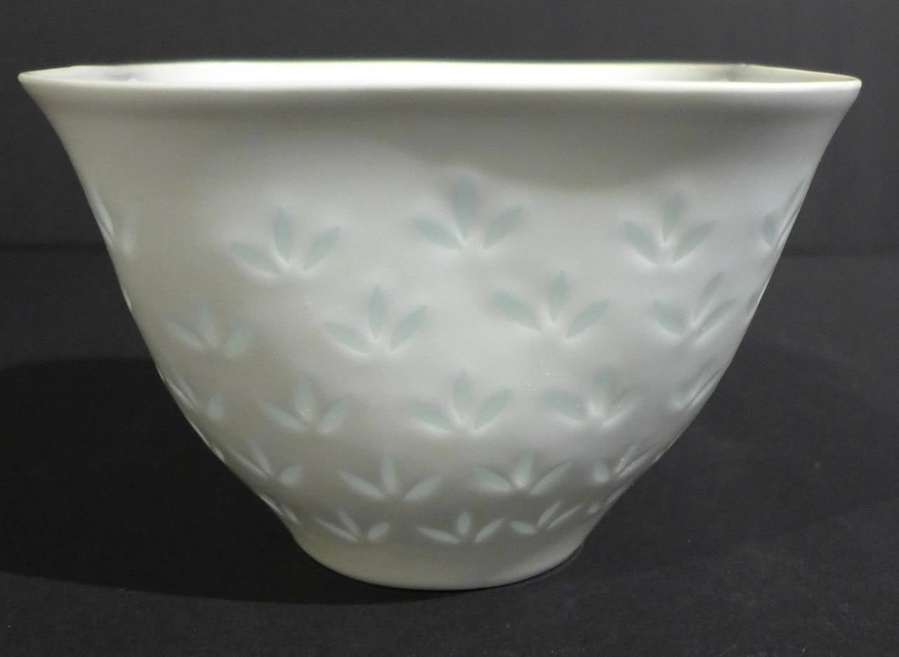 Delicate porcelain vessel with translucent, hand-cut rice motif, in the