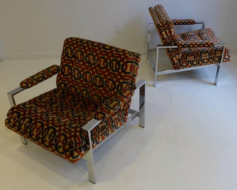 Pair of flat bar chrome lounge chairs designed by Milo Baughman and produced by Thayer Coggin, circa 1970s. Elegant, linear forms. The lack of a cross brace along the top rear gives a more open, sculptural look. The original fabric is still in fine