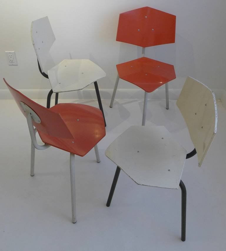 Set of four chairs produced circa 1950 by the Dutch company Auping, with tubular steel bases and hexagonal molded plywood seats and backs. Two matching chairs in black and white; two in white and coral. With original paint; in Fine condition with