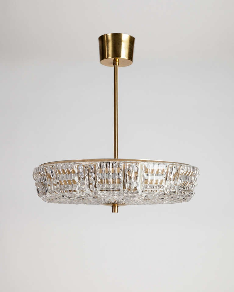 AHL3798  A cross-hatched textured glass pendant designed by Carl Fagerlund for the Swedish maker Orrefors. In its original age-worn brass finish.  DIMENSIONS Current height: 17-3/4