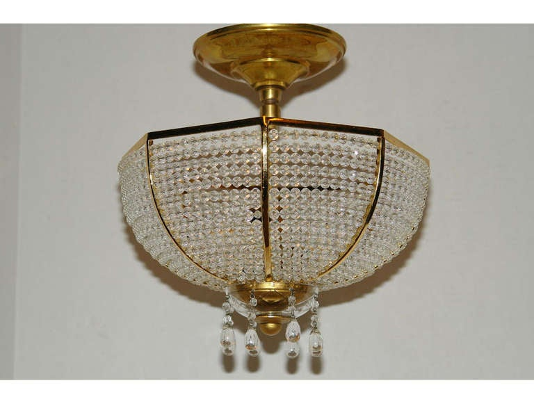 A circa 1930s French beaded crystal ceiling fixture with interior lights.  Measurements: Height 11